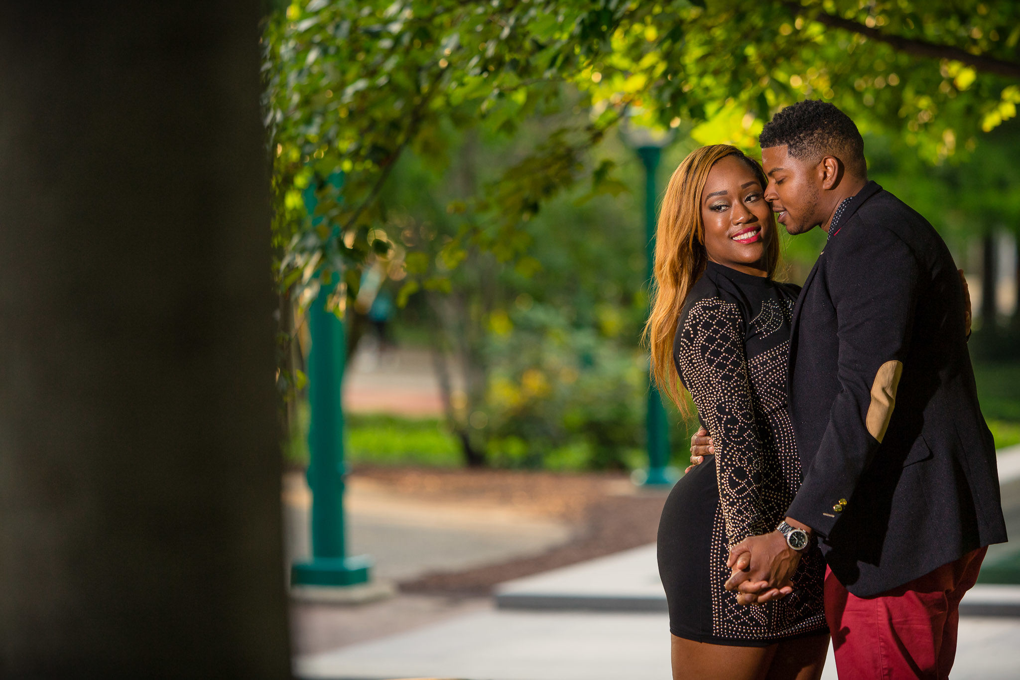 One of the best wedding photographers in Greenville SC portrait of an African American couple embracing for a candid portrait in Centennial Park