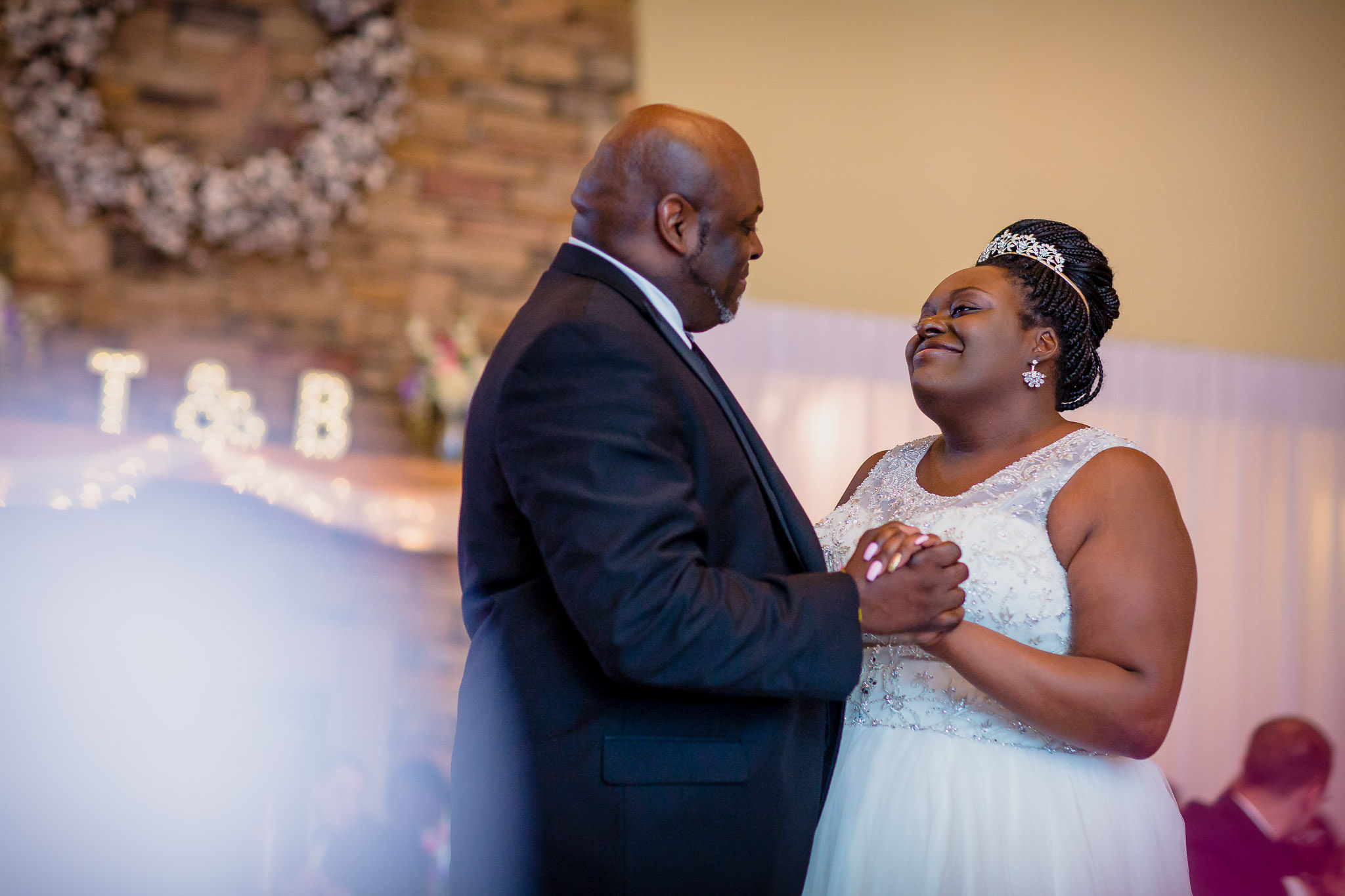 One of the best wedding photographers in Greenville SC photo of an African American father daughter dance at the Lodge at Lake Bowen