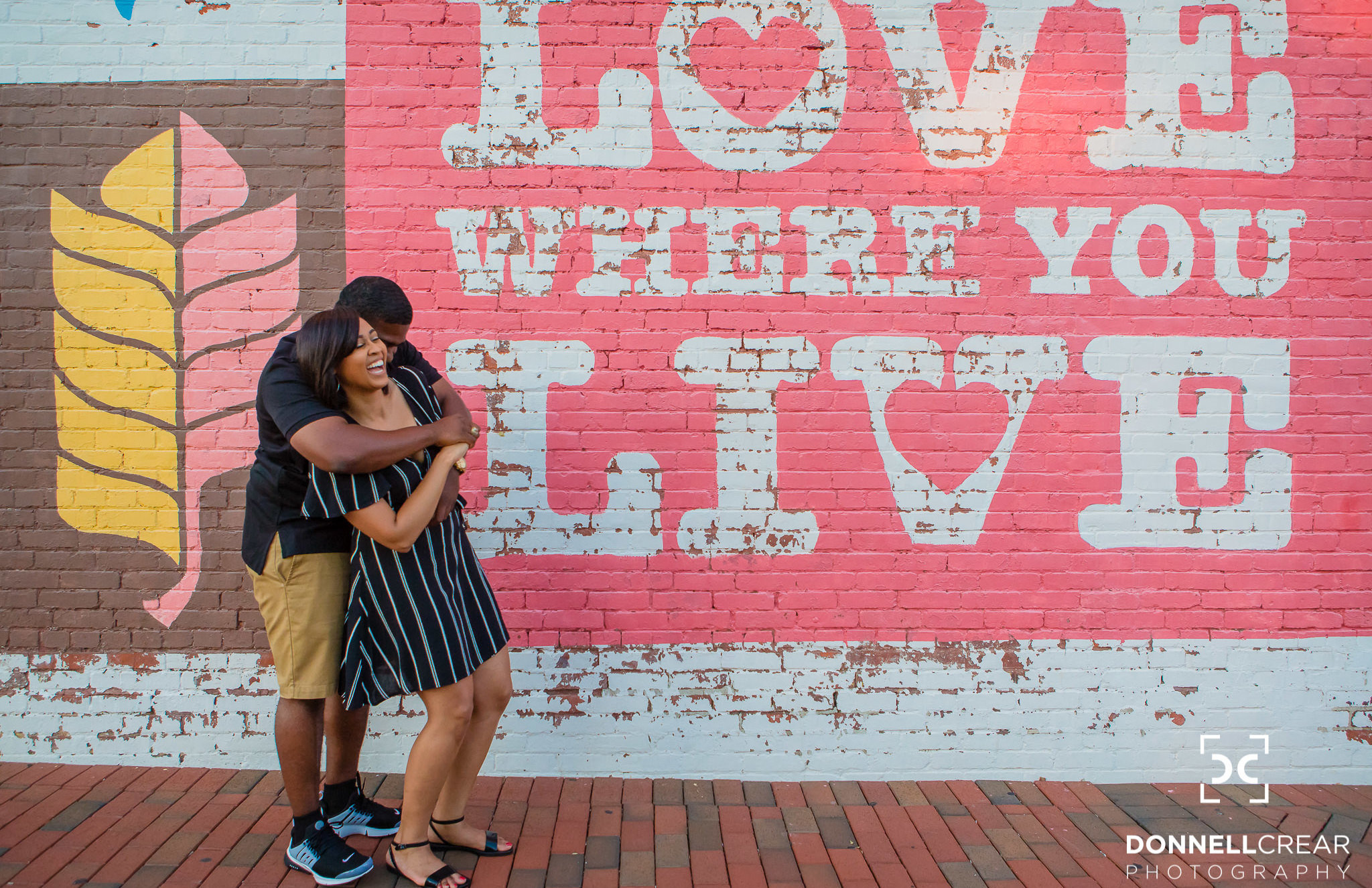 "African American couple hugging in front of the ""Love Where You Live"" mural during their Downtown Spartanburg engagement session"
