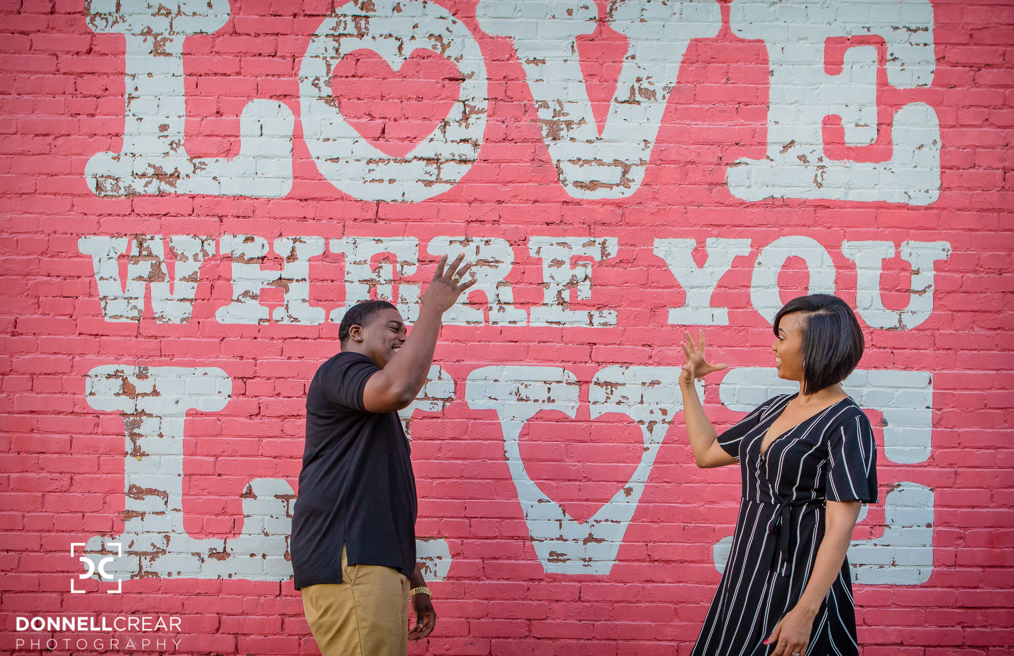 "African American couple doing their hand shake in front of the ""Love Where You Live"" mural during their Downtown Spartanburg engagement session"
