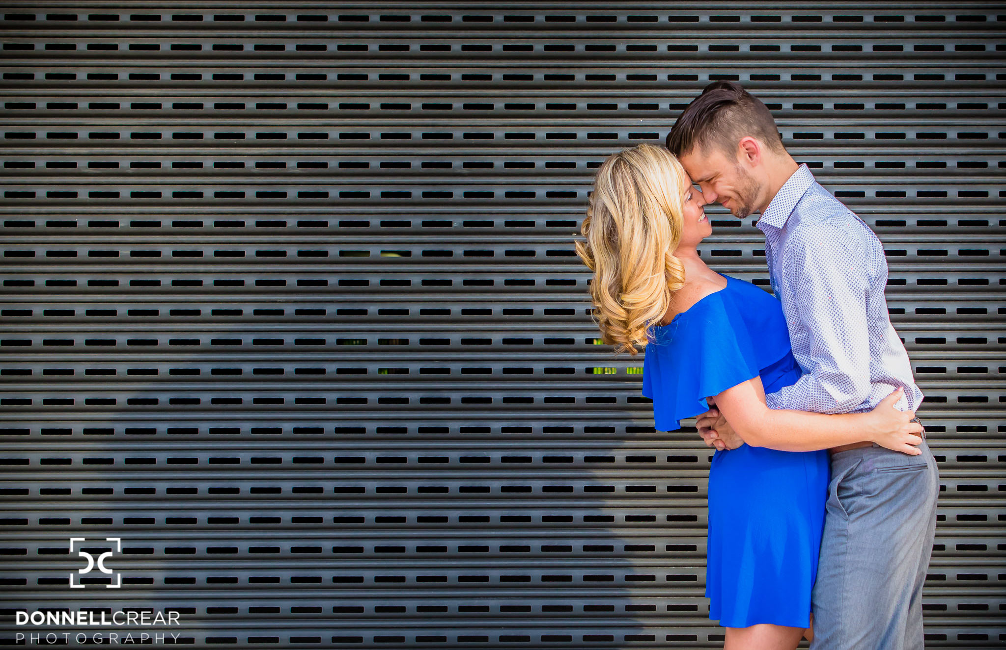 Engaged couple embracing in front of parking garage during their downtown Spartanburg engagement session