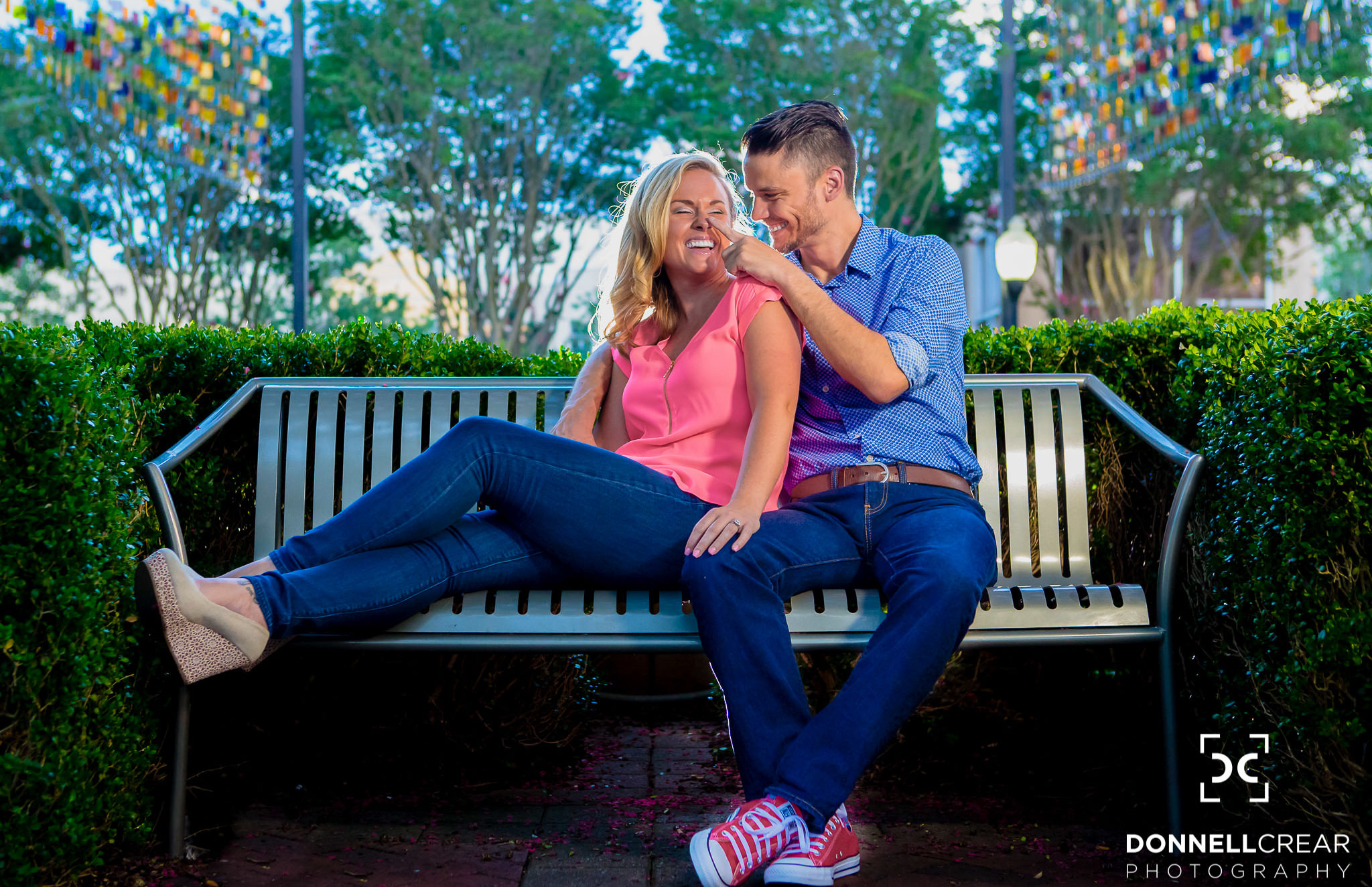 Engaged couple sitting on bench outside of the Denny's Headquarters during their engagement session