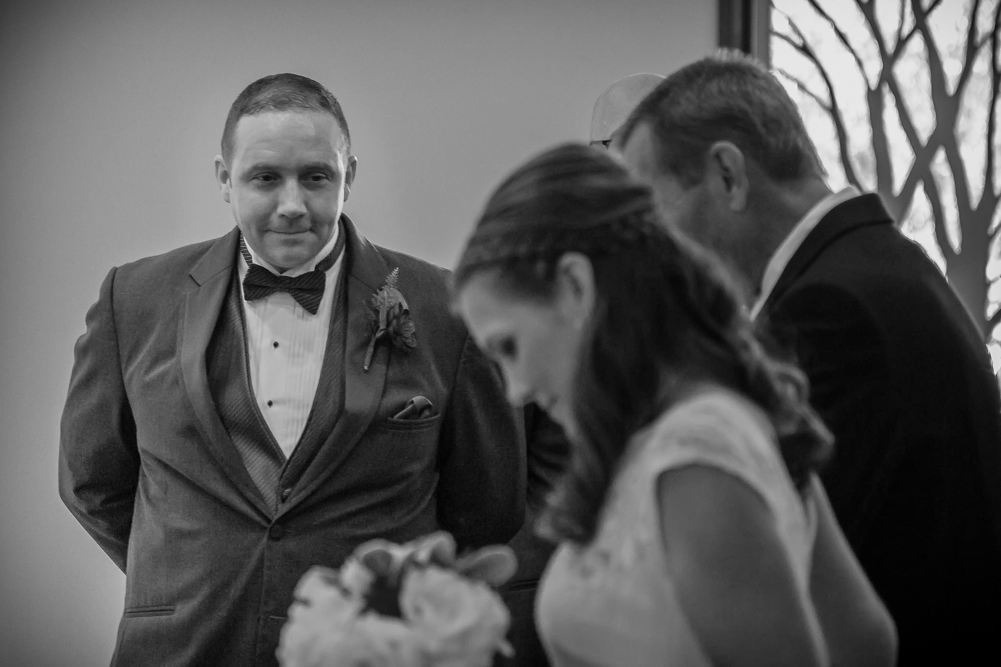 One of the best wedding photographers in Greenville SC photo of a groom watching his bride walk down the aisle
