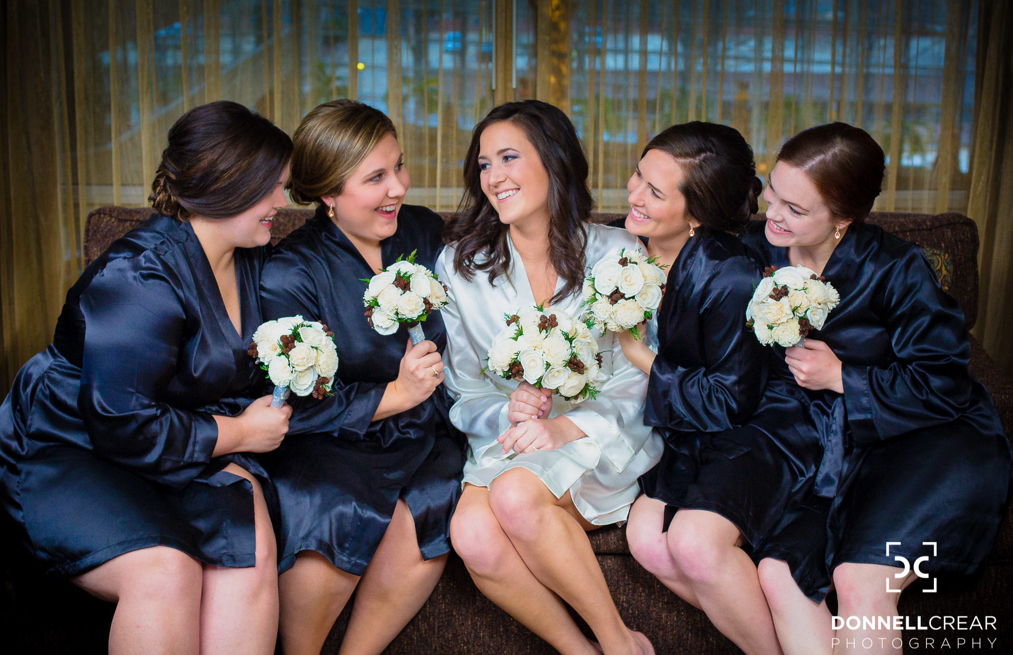 Bridal party embracing each other at their Hyatt Hotel suite before a Commerce Club wedding