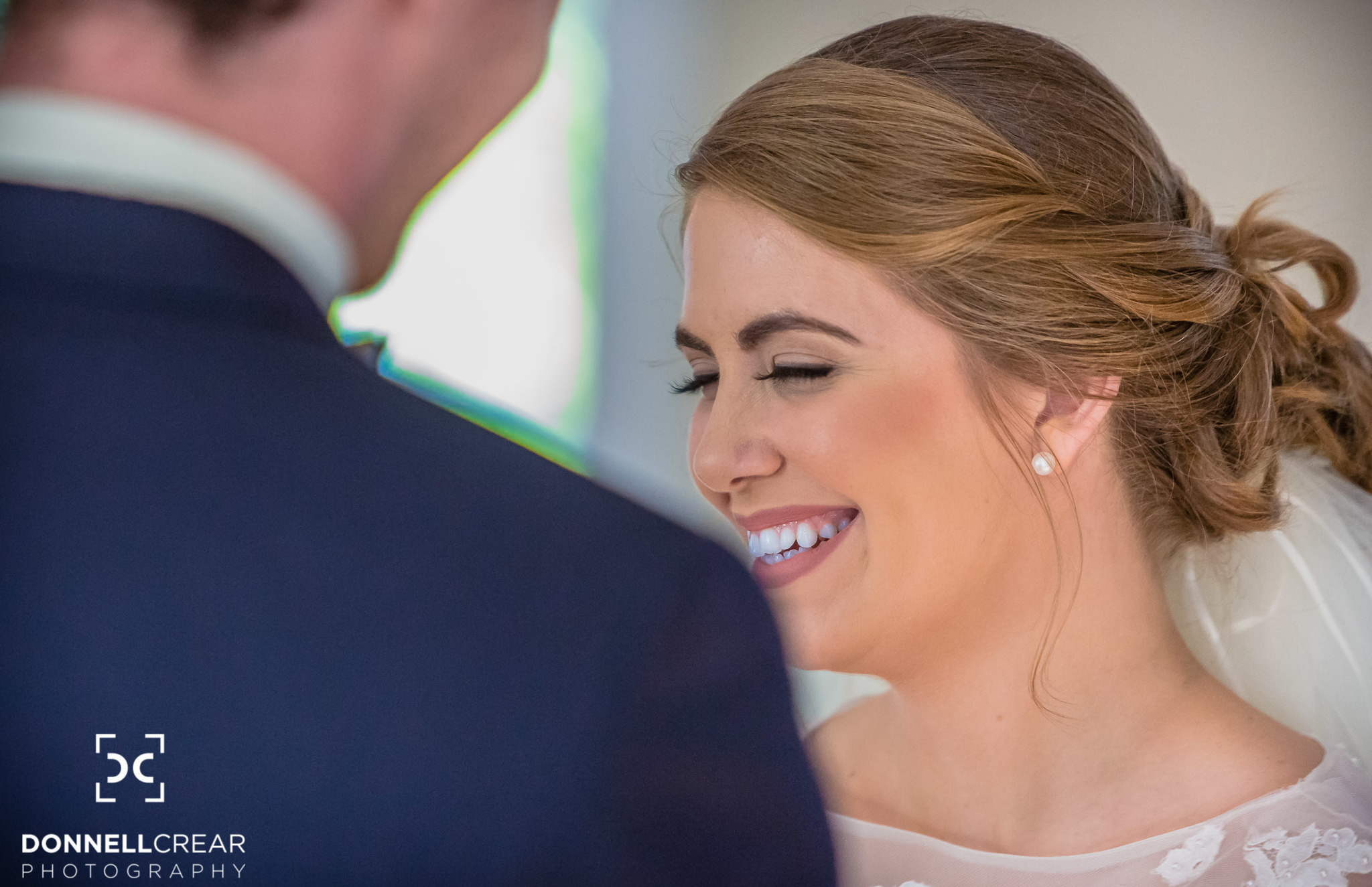 Bride laughing at something the groom said during the ceremony of their Cokesbury College wedding