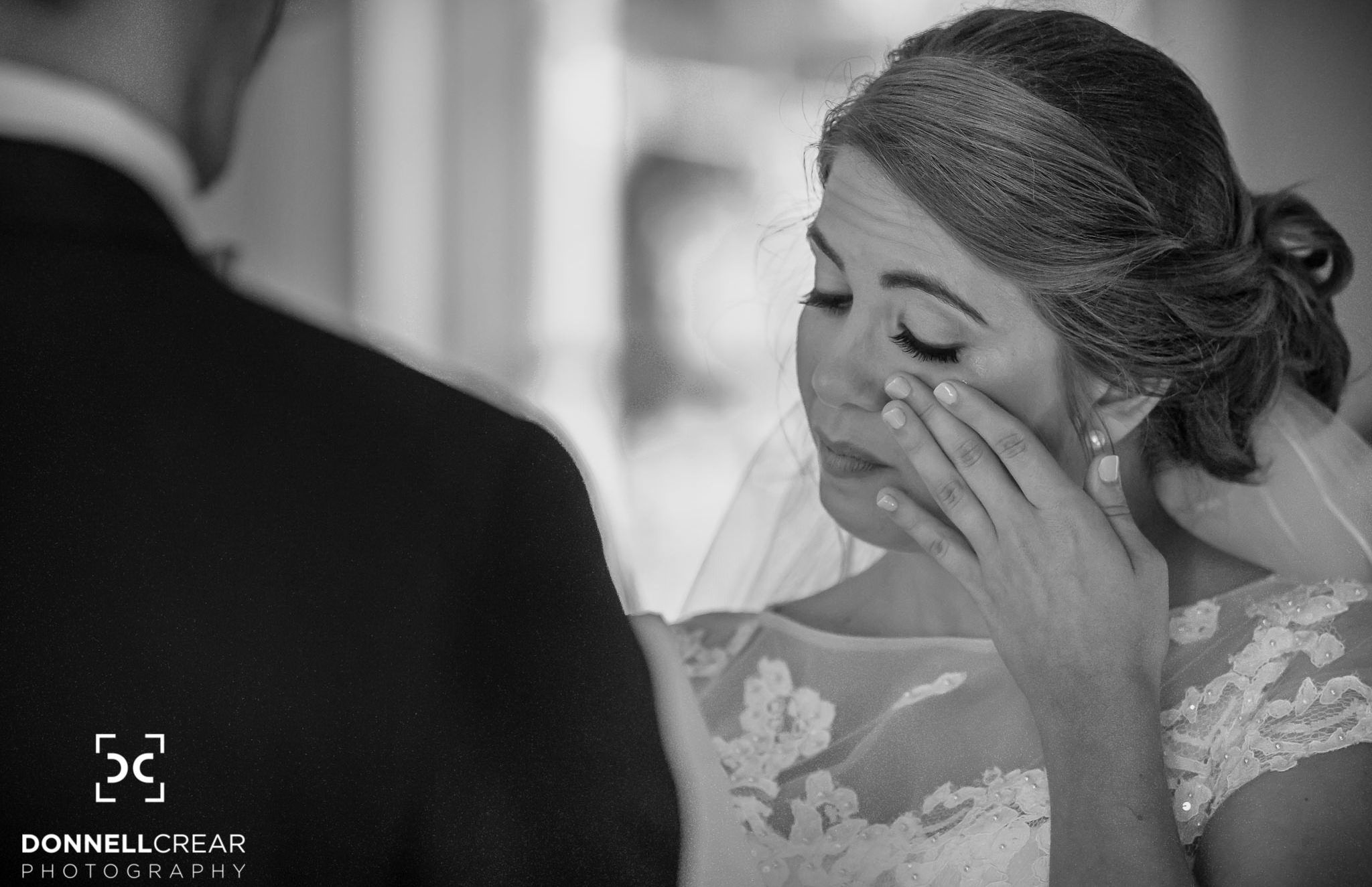 Bride wiping a tear away during her Cokesbury college wedding ceremony