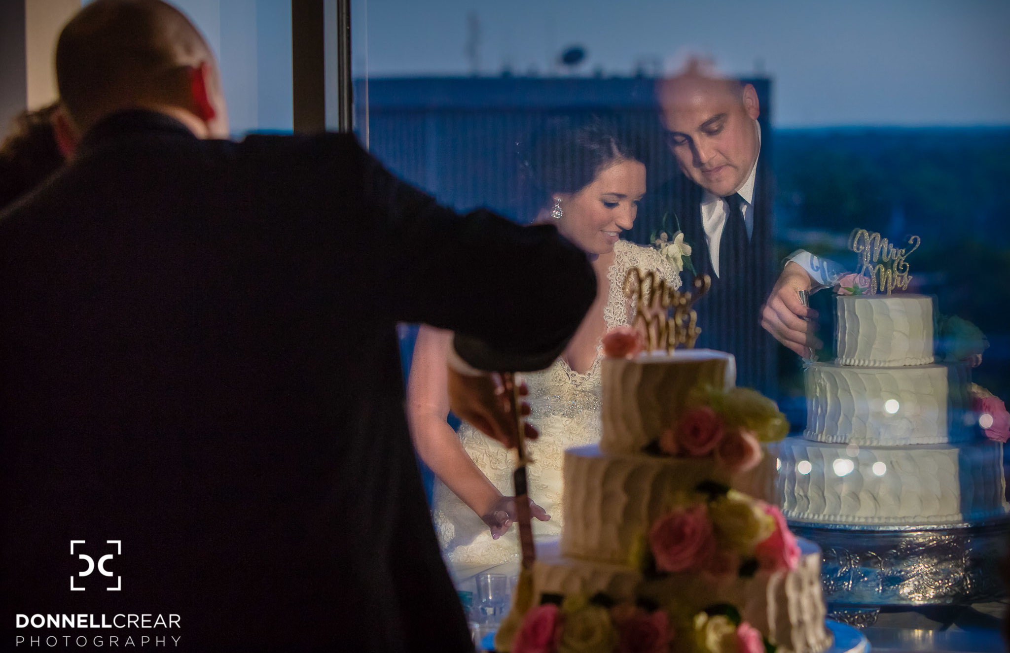 Couple cutting their wedding cake during their Commerce Club wedding overlooking downtown Greenville SC