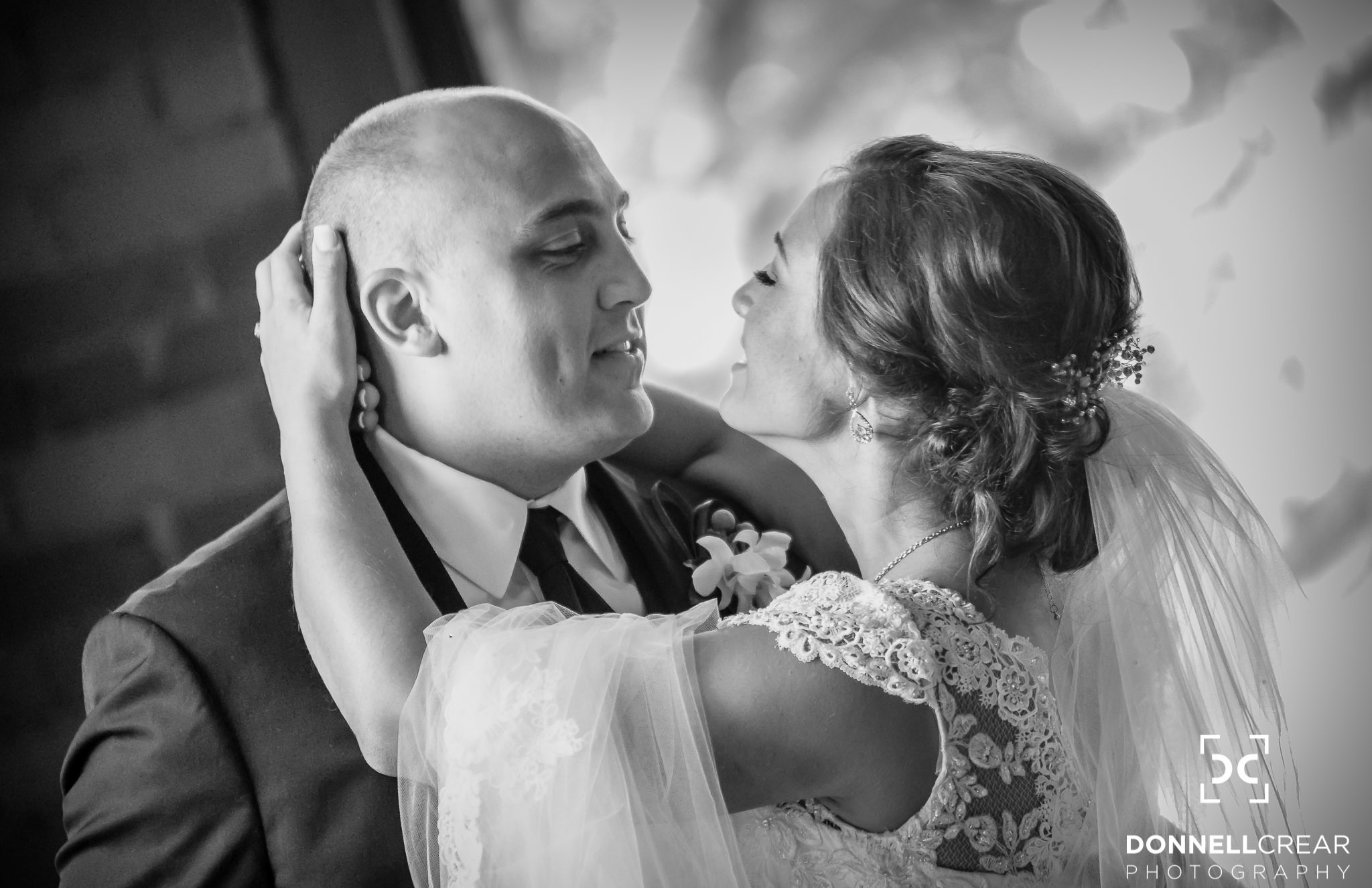 Bride embracing the back of her groom's head after their Commerce Club wedding