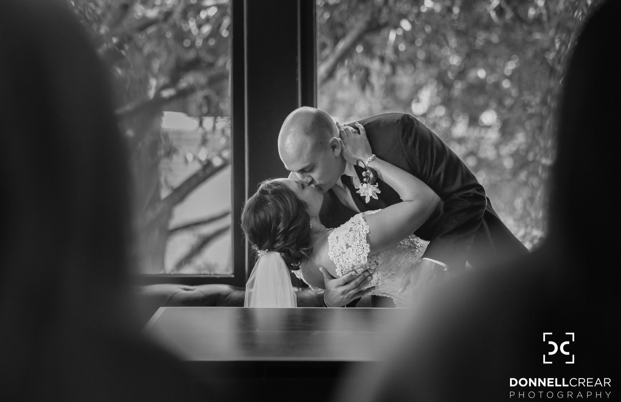 Groom dipping his bride and giving her a kiss during their Commerce Club wedding