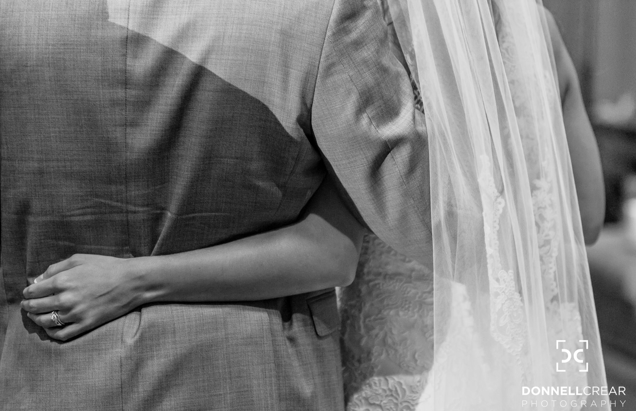Bride's arm around the waist of her groom as they listen to toasts during their Cleveland Park wedding reception