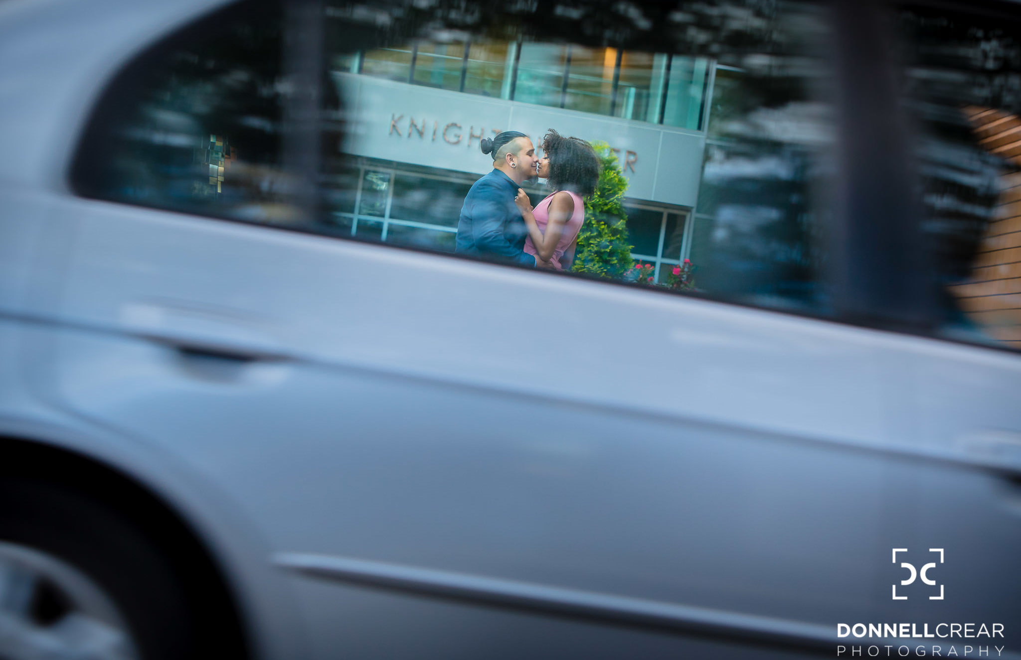 Uptown Charlotte Engagement Session in front of Bechtler Museum of Modern Art with couple kissing while framed in car window