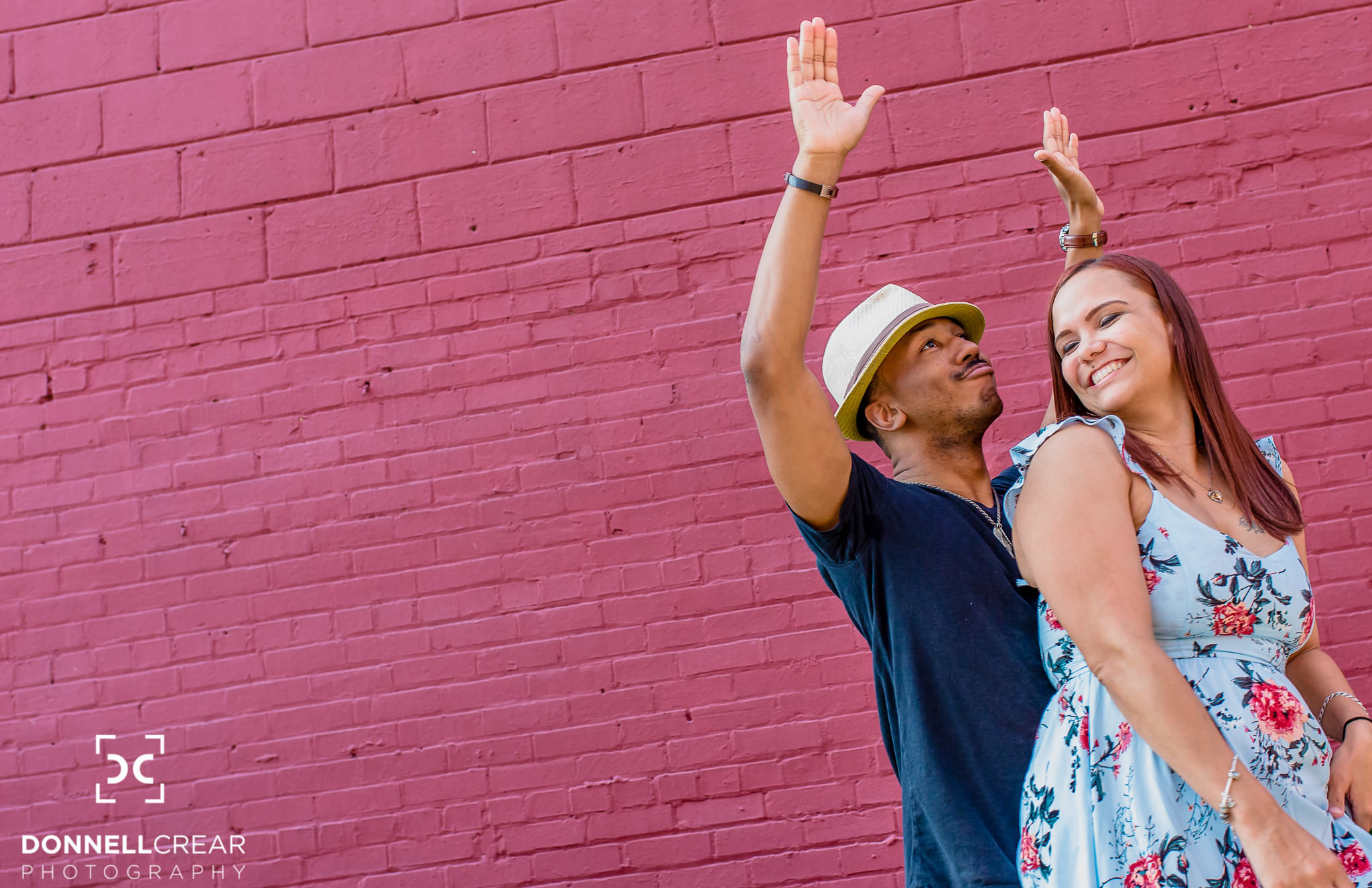 Interracial couple dancing in front of wall at NODA Charlotte engagement session