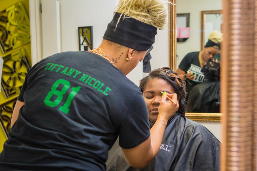 Tiffany Singleton of Tiffany Nicole Beauty applying makeup on a client